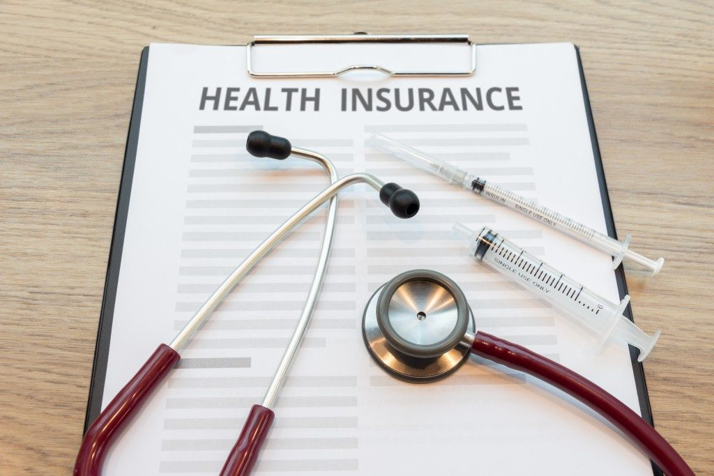 Health insurance form with stethoscope and syringe