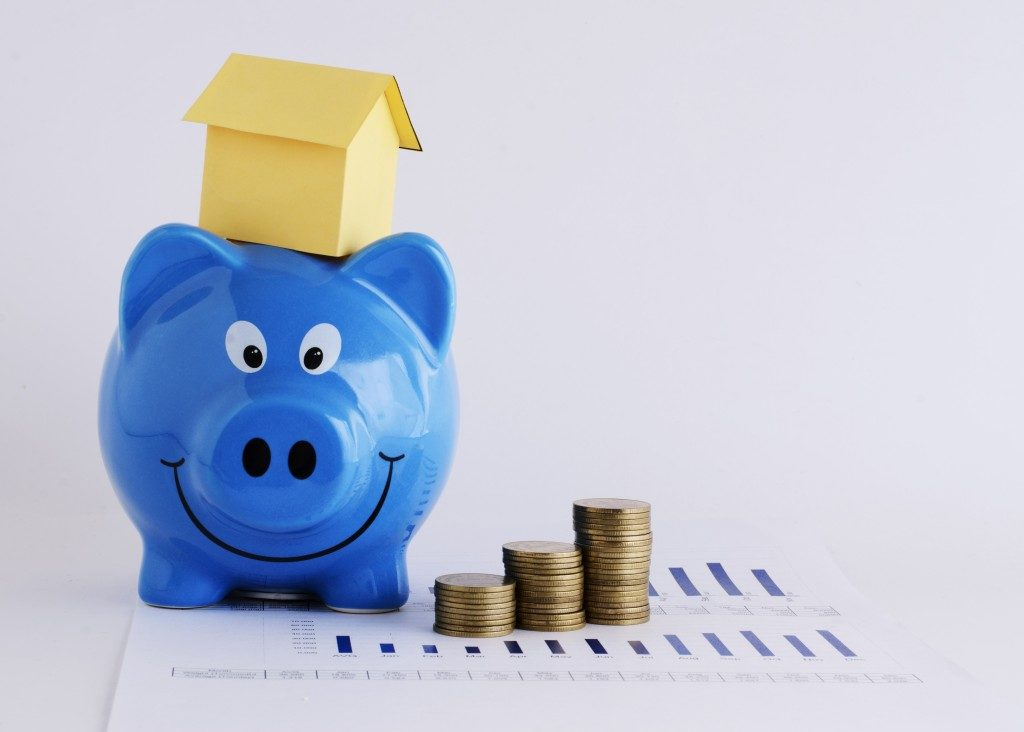 Piggy bank with a house model on top and coins
