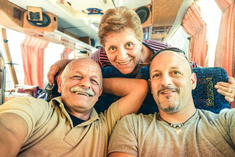 Man with his elderly parents in a tour bus