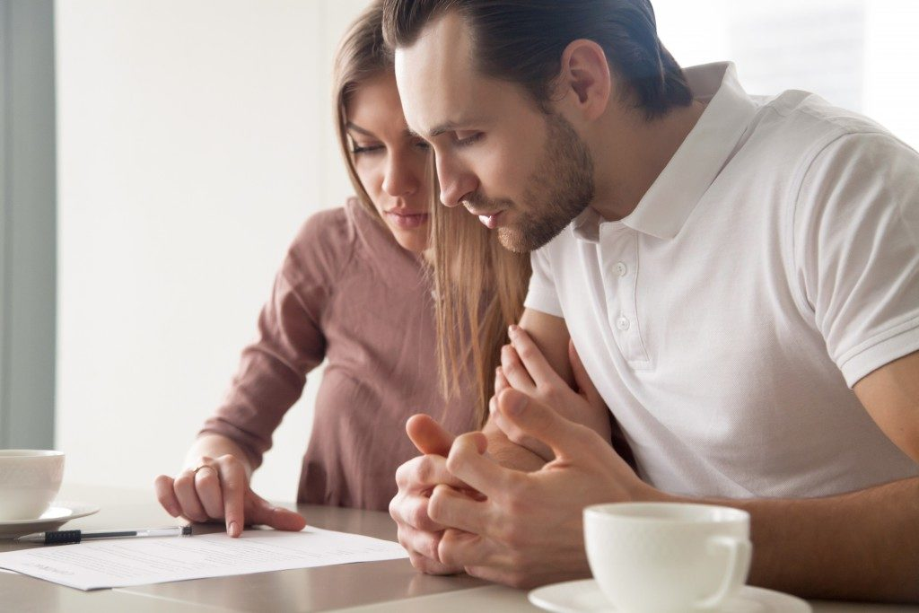 Couple reviewing a contract before finalizing a sale