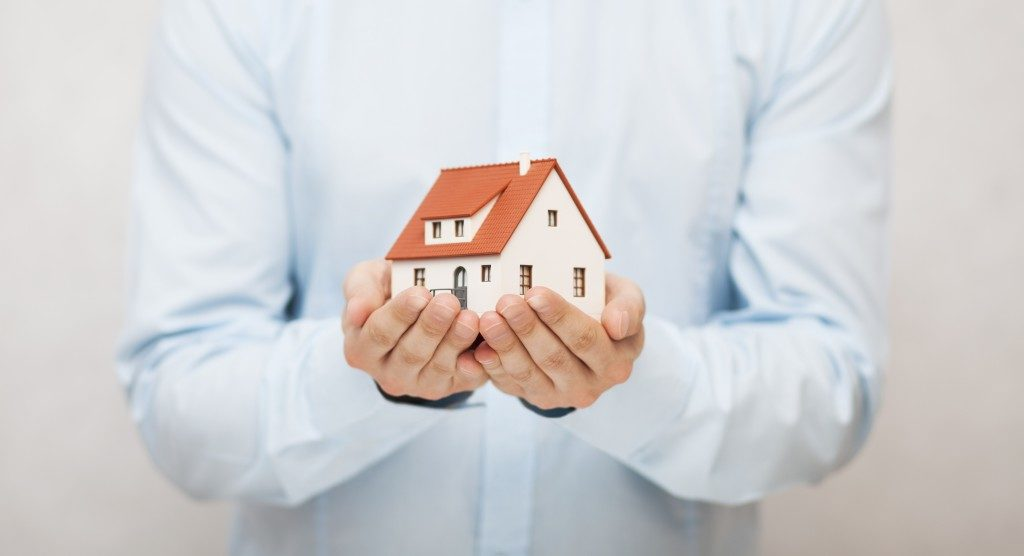 person holding a house miniature with both hands